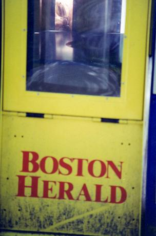 Looking through a Boston Herald newspaper box