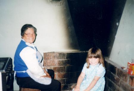 Nadia and grandma by the fireplace