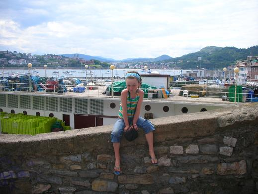 Isabelle sitting with the port of San Sebastian behind